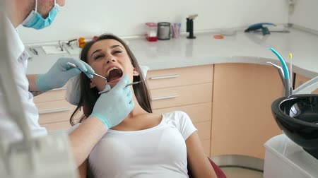 ağız : Closeup of dentist examining young womans teeth Stok Video