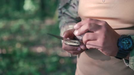 pain free : Close up of soldier sharpen knife with bilestone in the forest Stock Footage