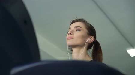 aeróbica : Close-up of a girl with headphones on a treadmill