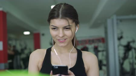 teen action : Close-up of a girl with headphones on a treadmill. 4k Stock Footage