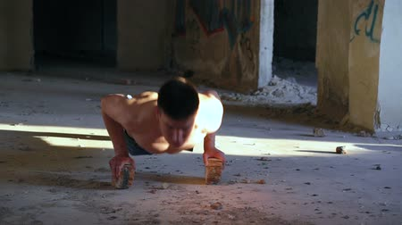 catacomb : Strong man doing push ups with bricks in catacomb Stock Footage