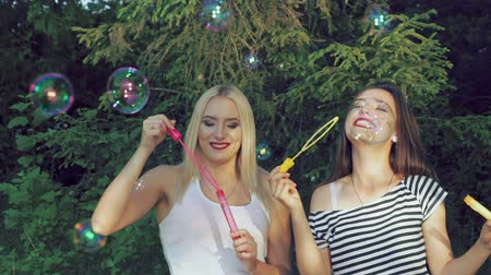 darbe : Happy girls blowing colourful soap bubbles in summer park. Slowly