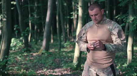 pain free : Military sharpen knife with bilestone in the forest. Slow motion