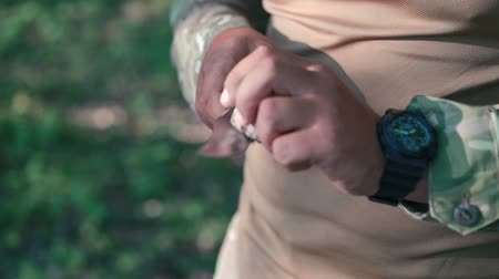 pain free : Close up of soldier sharpen knife with bilestone in the forest. Slow motion