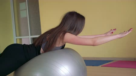 sapma : The girl in sportswear doing deflection back exercises with fitball 4k