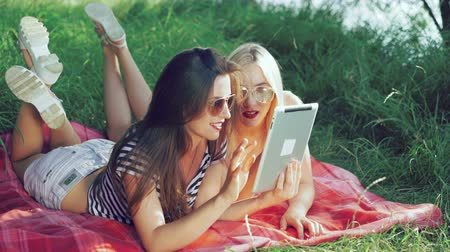 despreocupado : Pretty carefree girls lying on blankets on the grass and using the tablet. 4k