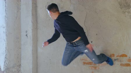 catacomb : A free runner back flips off a wall. Slowly Stock Footage