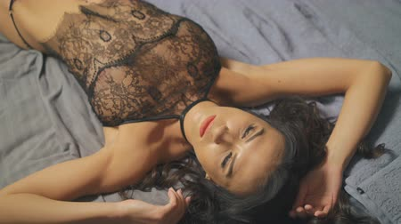 spodní prádlo : Sexy woman with attractive body in lace lingerie lying on bed. 4K Dostupné videozáznamy
