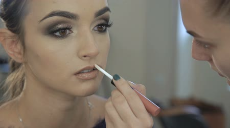 косметика : Close up of make up artist applying lipstick pencil on lips Стоковые видеозаписи