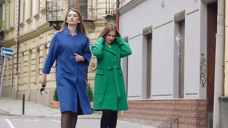 tripping : Two assured women walks runway in cashmere wool coats on the street. Slowly Stock Footage