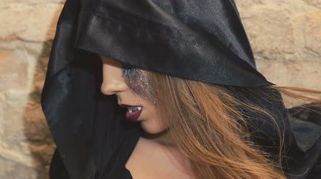 possessed : Female enchantress in the black coat scaring with her teeth on the camera Stock Footage