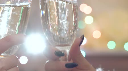 bolha : Two glasses with champagne toasting over holiday blinking background. Slowly