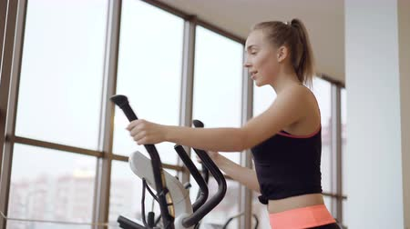 trabalhar fora : Look of the girl working out with the bicycle simulator in the gym 4K Vídeos