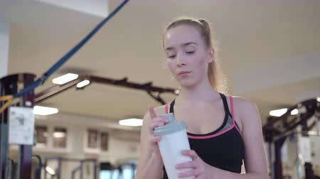 caucasiano : Attractive caucasian girl is drinking a protein shake drink in the gym 4K