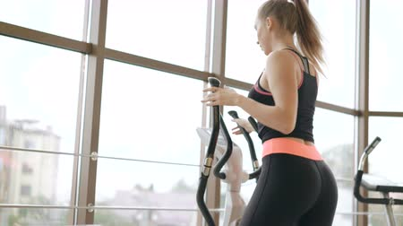 trabalhar fora : Back look of the girl working out with the bicycle simulator in the gym 4K