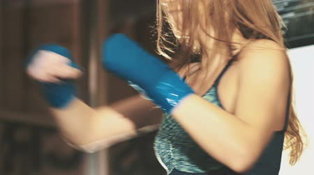 zsák : Pretty kickboxing girl training with punching bag in a fitness gym. Slowly