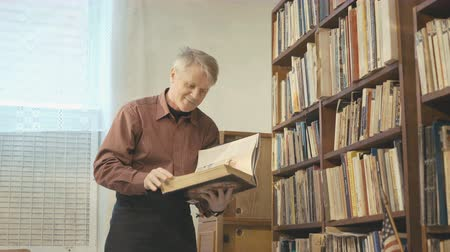söyleme : The old man flipping through the book in the room 4k Stok Video