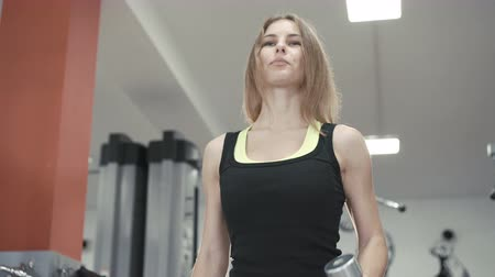 бицепс : Young girl working out with dumb-bells for biceps in the gym 4K Стоковые видеозаписи