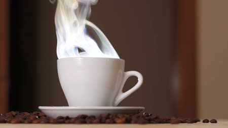 evaporate : Close up of a white cup of evaporating coffee on table near roasted beans