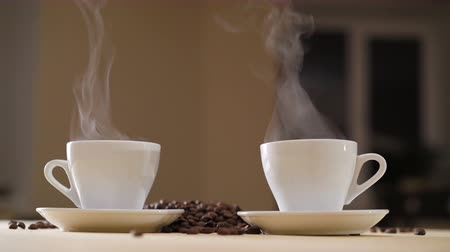 evaporate : Two white cups of delicious coffee on the table with roasted beans in 4K