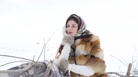 cold : Young girl in winter clothes waiting near fence and looking aside 4K