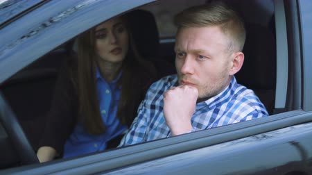 gritar : Unhappy man arguing in car, while woman calms him in 4K