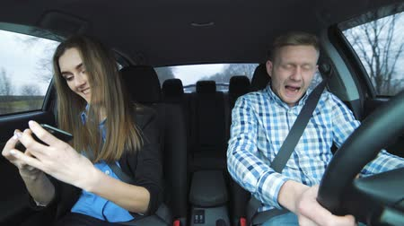 inside car : Glamorous couple riding in car, dancing, singing and taking selfies Stock Footage