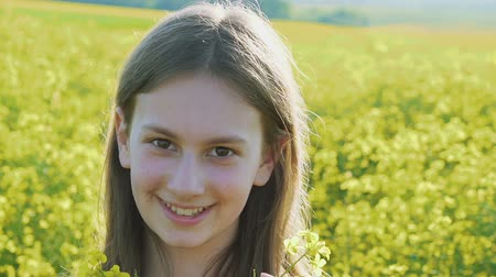 repce : Smart young girl stands with rape flowers and smiling at camera in rapes field Stock mozgókép
