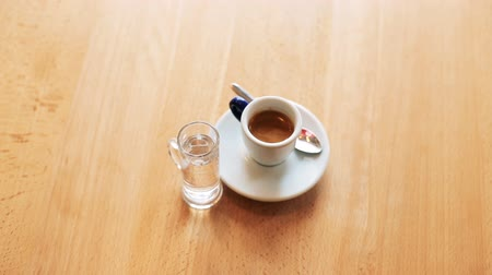 сироп : View of a cup of coffe with glass of water on background