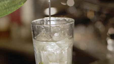 ice cube : Pouring water into glass for lemonade. Slowly