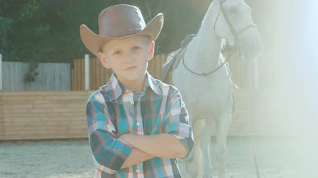 dazzle : Portrait of little cowboy with crossed hands near horse on sunlight. Slowly Stock Footage