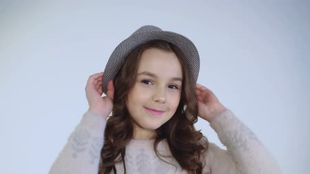 camera move : Pretty young girl plays with hat and wears on head with cute smile