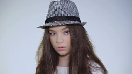 seriously : Beautiful young model lifts head in hat and looks at camera enigmatically Stock Footage
