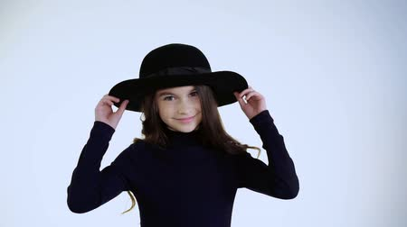 seriously : Beautiful young and happy model in hat, nods head and looks at camera
