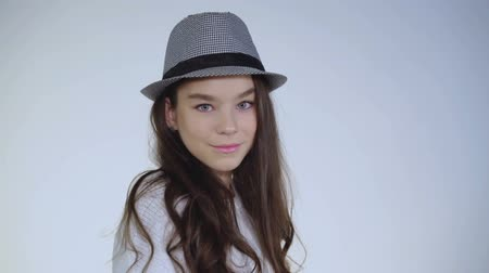 да : Pretty young girl plays with hat and wears on head with cute smile