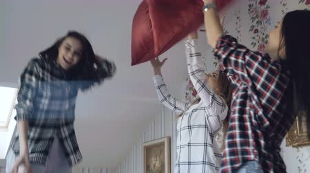 восхищенный : Three young pretty girls jumping on bed and fight pillows having fun at home Стоковые видеозаписи