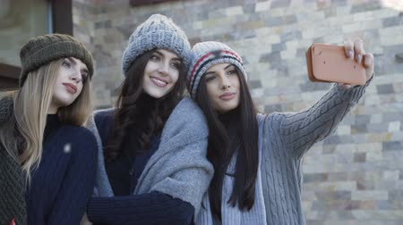 перемычка : Three pretty smiling girls in caps and scarf taking selfie on the yard Стоковые видеозаписи