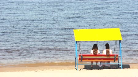 wistful : Romantic couple sitting on a swing on the beach. Two girls in love Stock Footage