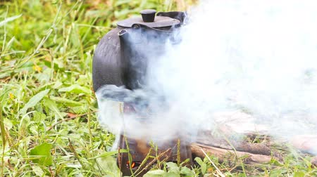 wood burner : The smoked kettle is heated on the camp portable stove Stock Footage