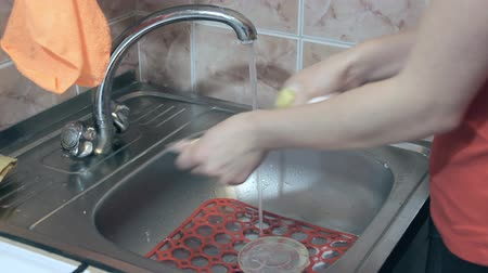lavatório : Girl washing dishes in a sink