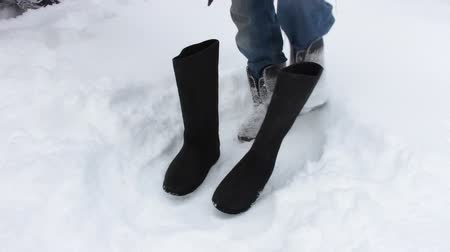 fur boots : A woman in jeans takes off a felt boot and puts on a sock