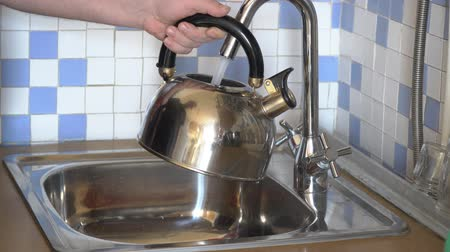 korsó : A man pours water into a kettle from a tap