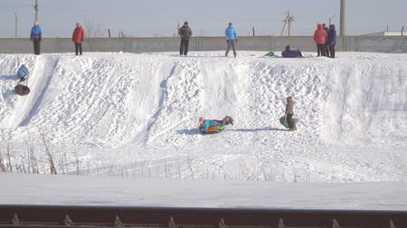 escorregadio : CHAPAEVSK, SAMARA REGION, RUSSIA - MARCH 28, 2018: People stand on the hill and watch as children are sledding