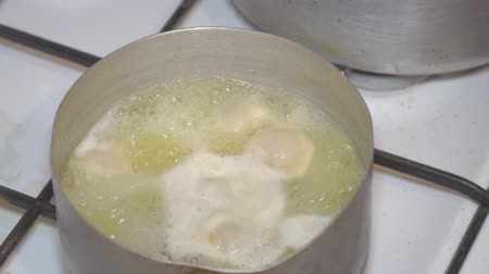 клецка : The soup broth is boiling in a small saucepan. Cooking dumplings.