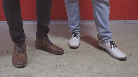 impatience : The legs of two men in shoes. Boots of white and brown colors Stock Footage