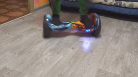 нога : A teenager uses hoverboard in his home room. Spinning on a hyroscooter