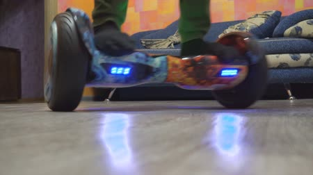 balanceamento : A teenager uses hoverboard in his home room. Spinning on a hyroscooter