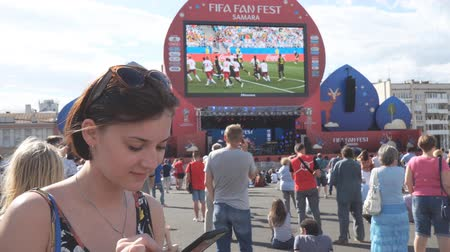 fan fest : SAMARA, RUSSIA - JUNE 21, 2018: Girl with a phone in the fan zone of the FIFA world Cup 2018 in Samara on the area of Kuibyshev Stock Footage