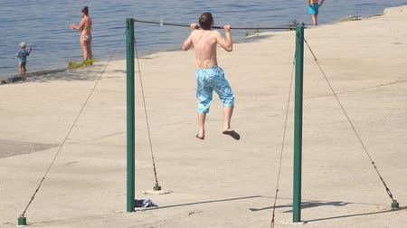 hand on chin : SAMARA, RUSSIA - JUNE 19, 2018: Young man pulling up on the bar. Beach, sports ground, pull-up on the bar Stock Footage