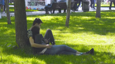 caráter : Russia, Samara, May 27, 2018: Loving couple sitting on the lawn in the Park Stock Footage
